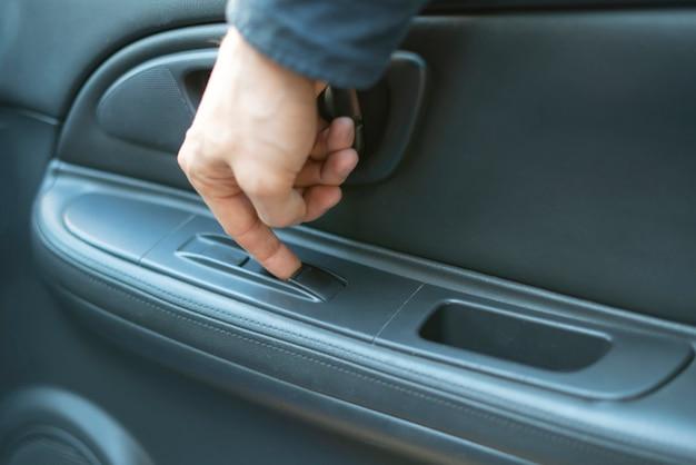 Uma pessoa sentada dentro do carro e abrindo a janela aperta o botão com o dedo