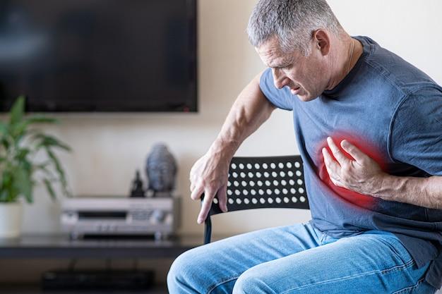 Uma pessoa sente dor no peito causada por um ataque cardíaco. doença cardíaca. angina pectoris. o conceito de seguro saúde para idosos.