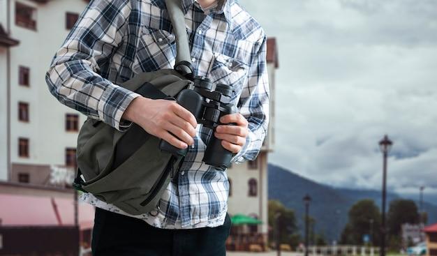 Uma pessoa tirando o binóculo da bolsa e ajustando-o
