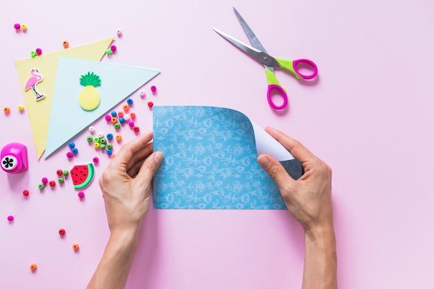Uma pessoa transformando o papel de scrapbook azul com itens decorativos em fundo rosa