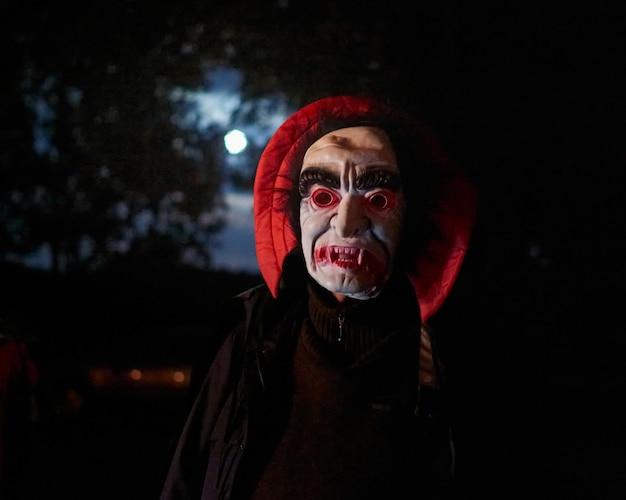 Uma pessoa usando uma máscara de drácula assustadora à noite com a lua cheia atrás