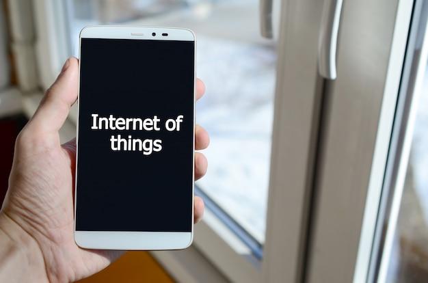 Uma pessoa vê uma inscrição branca em uma tela preta de smartphone que segura na mão.
