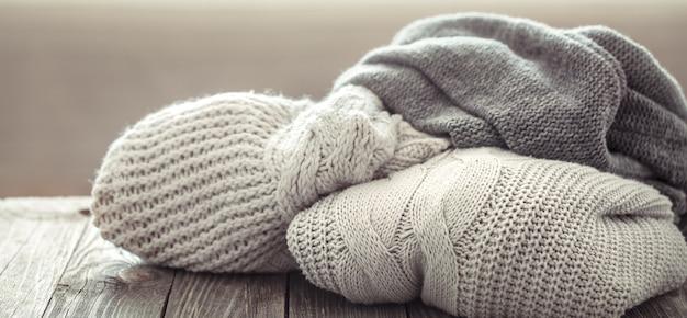 Uma pilha aconchegante de suéteres de malha em uma mesa de madeira