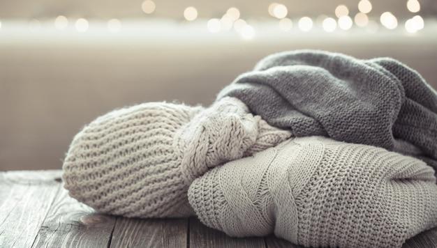Uma pilha aconchegante de suéteres de malha em uma superfície de madeira