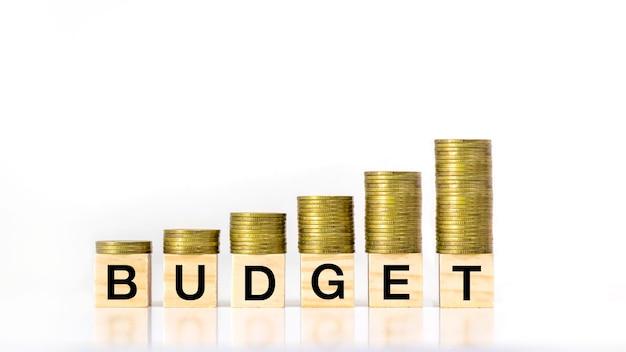 Uma pilha crescente de moedas pisa em um bloco de madeira rotulado como orçamento em um fundo branco, ideia de orçamento de investimento e orçamento anual.