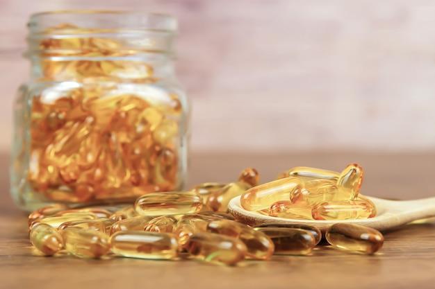 Uma pilha da cápsula do óleo de fígado de bacalhau em uma colher de madeira.