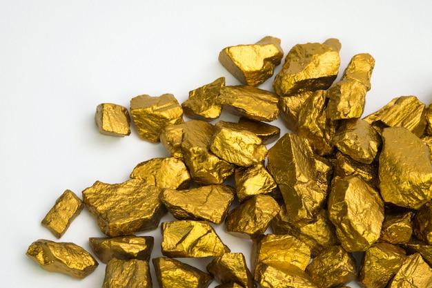 Uma pilha das pepitas de ouro ou do minério de ouro isoladas no fundo branco, na pedra preciosa ou na protuberância do conceito dourado da pedra, o financeiro e do negócio.