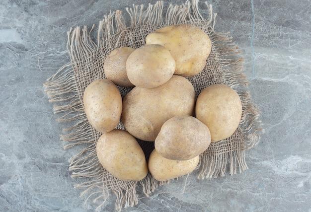 Uma pilha de batatas no tripé sobre a mesa de mármore.