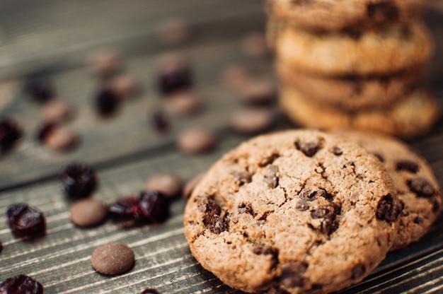Uma pilha de biscoitos de aveia com pedaços de chocolate e frutas cristalizadas situa-se em uma mesa de madeira