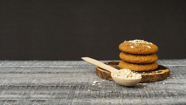 Uma pilha de biscoitos de aveia e uma colher de pau com aveia em flocos