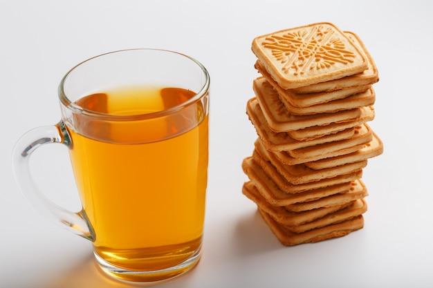 Uma pilha de biscoitos de trigo dourado e uma caneca de chá verde perfumado em cinza