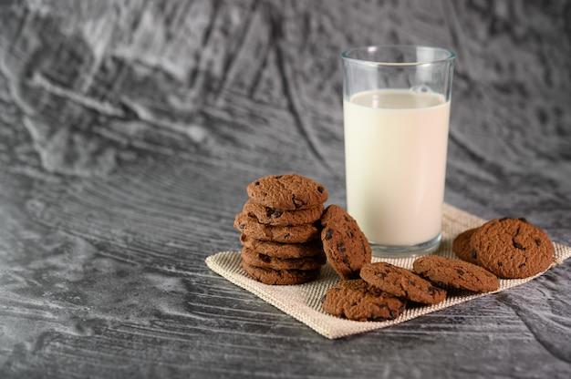 Uma pilha de biscoitos e um copo de leite em um pano sobre uma mesa de madeira