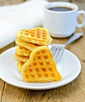 Uma pilha de biscoitos em forma de coração com um garfo em um prato branco, a xícara e o guardanapo em um fundo de tábuas de madeira