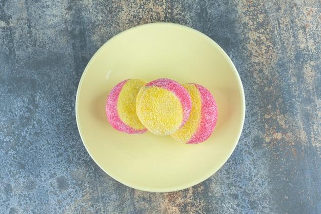 Uma pilha de biscoitos em forma de pêssego no prato, na superfície do mármore.