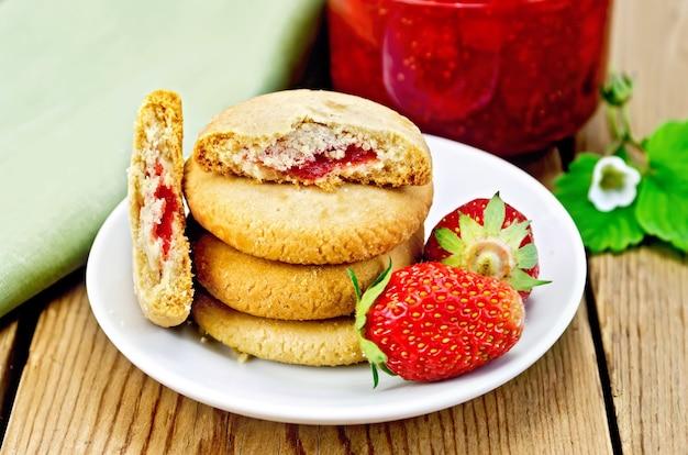 Uma pilha de biscoitos recheados com geléia e morangos em um prato, um pote de geléia de morango no fundo de tábuas de madeira