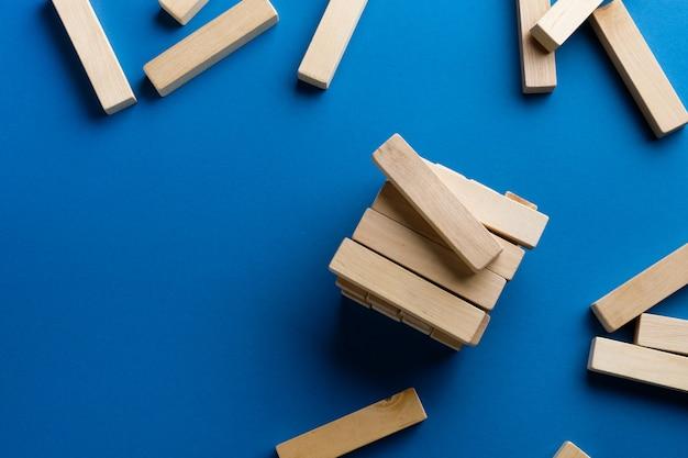 Uma pilha de blocos de madeira dispersados em uma superfície azul. jogo de construção. a torre quebrada.