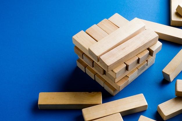 Uma pilha de blocos de madeira espalhados sobre um fundo azul. jogo de construção. a torre quebrada.