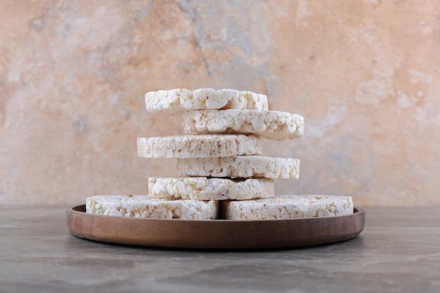 Uma pilha de bolos de arroz tufado na bandeja de madeira, na superfície de mármore