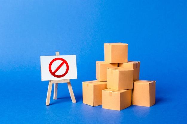 Uma pilha de caixas de papelão e uma placa com o símbolo vermelho não restrição à importação de mercadorias