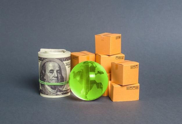 Uma pilha de caixas, um pacote de dólares e um planeta verde terra globo. comércio mundial