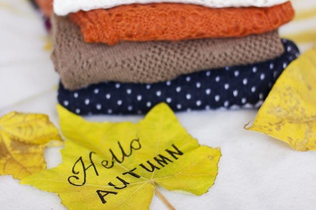 Uma pilha de camisolas quentes e uma folha de bordo amarelo