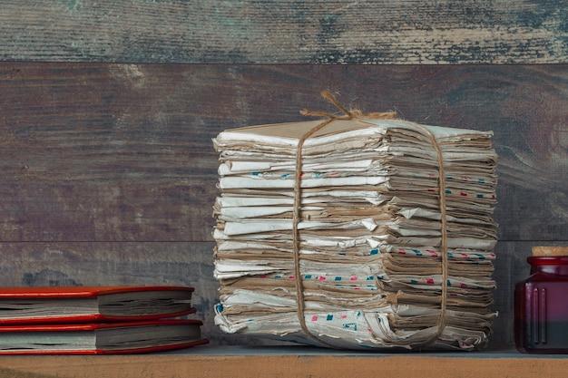 Uma pilha de cartas antigas e dois álbuns de fotos vermelhos estão sobre a mesa