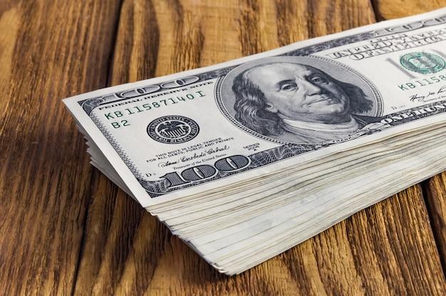 Uma pilha de cem notas americanas do dólar jogadas em uma tabela de madeira da textura.
