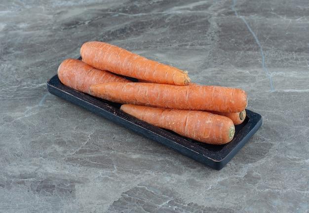 Uma pilha de cenouras na mesa de mármore.