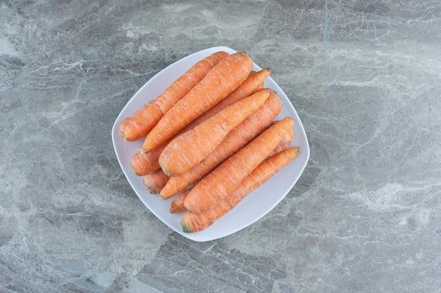Uma pilha de cenouras no prato, na mesa de mármore.