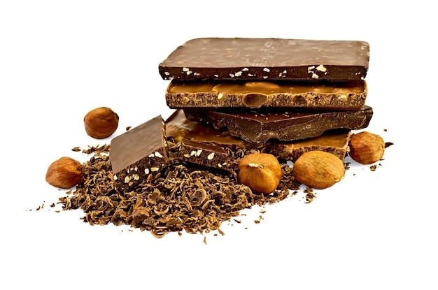 Uma pilha de chocolates diferentes, muito chocolate ralado com duas fatias de chocolate com nozes
