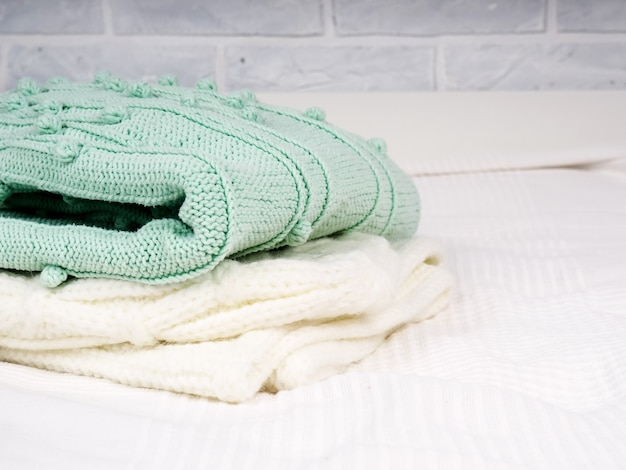 Uma pilha de coisas quentes tricotadas em uma cama branca. roupas aconchegantes. conceito doméstico. coisas de malha dobradas brancas.