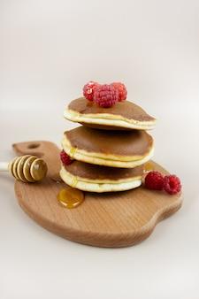 Uma pilha de deliciosas panquecas caseiras com framboesas, derramadas com mel e uma colher em uma bandeja de madeira.