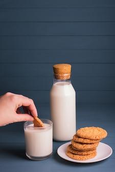 Uma pilha de deliciosos biscoitos caseiros em um prato branco, uma garrafa de leite e um copo de leite em um fundo azul de madeira