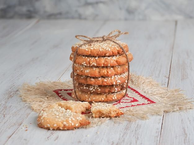 Uma pilha de deliciosos biscoitos de gergelim fresco em uma mesa de madeira branca