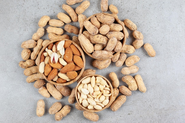 Uma pilha de diferentes tipos de nozes em tigelas ao lado de amendoins espalhados na superfície do mármore.