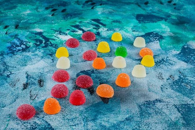 Uma pilha de doces de geleia, sobre o fundo azul.