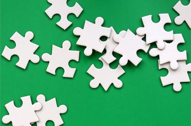 Uma pilha de elementos uncombed de um quebra-cabeça branca encontra-se no fundo