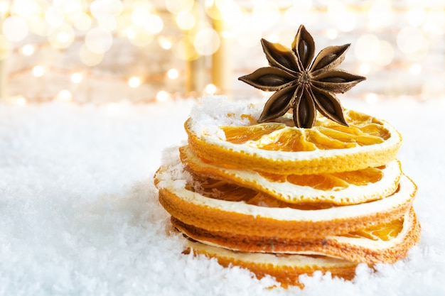 Uma pilha de fatias de laranja secas e anis estrelado na neve.