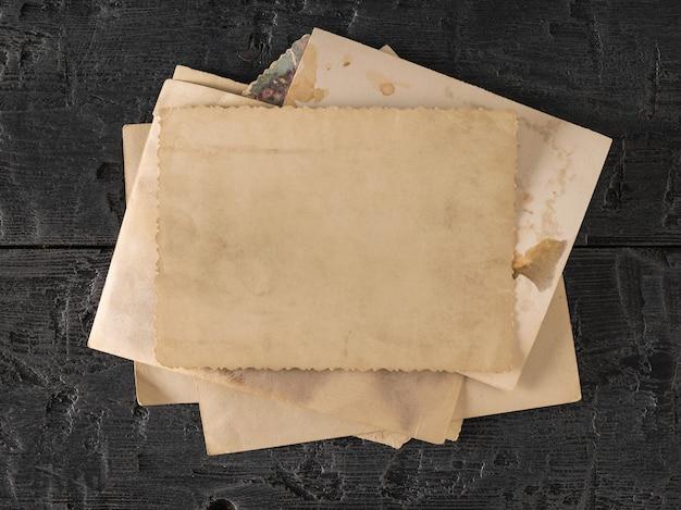 Uma pilha de fotos antigas em uma mesa de madeira preta. o assunto dos valores familiares. a vista do topo. postura plana.