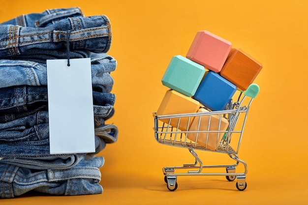 Uma pilha de jeans com uma etiqueta em branco em um amarelo