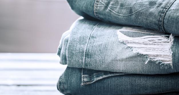 Uma pilha de jeans em um fundo de madeira