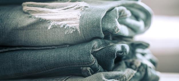 Uma pilha de jeans em uma mesa de madeira