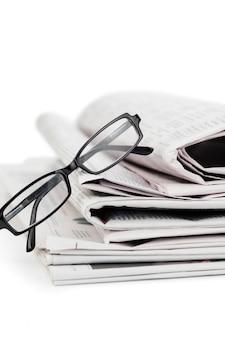 Uma pilha de jornais e um par de óculos de leitura