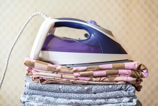Uma pilha de lençóis de cama de têxtil cobertores com ferro por cima