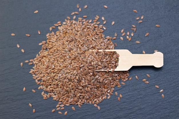 Uma pilha de linho ou sementes de linho em uma colher de pau
