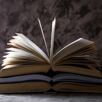 Uma pilha de livros abertos com páginas lançadas sobre um fundo cinza.