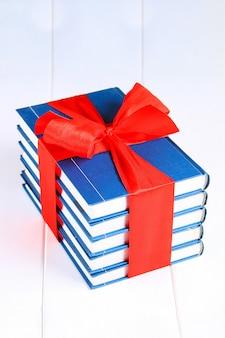Uma pilha de livros amarrados com uma fita vermelha em uma mesa de madeira branca.
