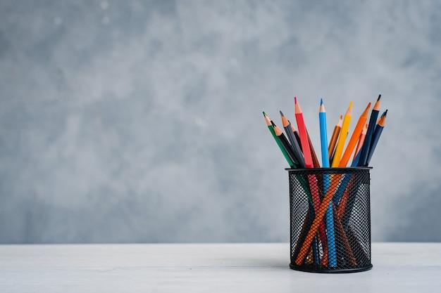 Uma pilha de livros coloridos e um copo de lápis brilhantes em uma mesa cinza-azulada. conceito de educação, treinamento, espaço de trabalho, espaço livre.