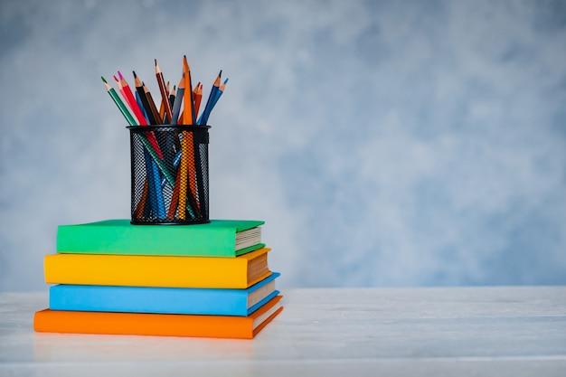 Uma pilha de livros coloridos e um copo de lápis brilhantes sobre um fundo cinza-azul.
