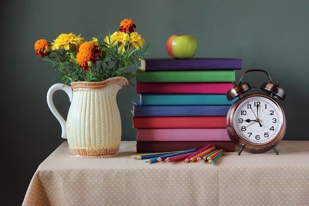 Uma pilha de livros com capas brilhantes, buquê, relógio, apple e lápis de cor